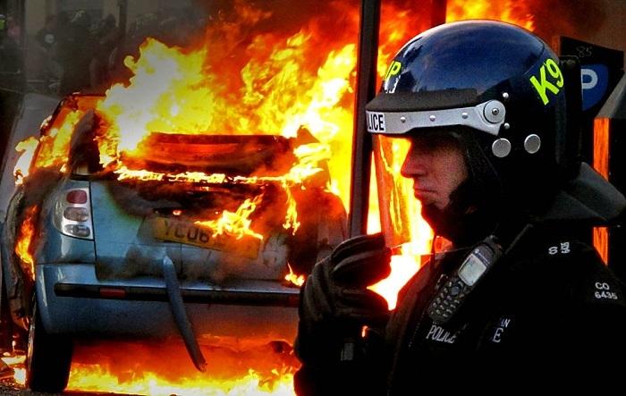 brytyjski-policjant-na-tle-palacego-sie-samochodu-podczas-zamieszek-w-londynie-sierpien-2011.jpg
